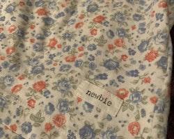 Vitt linne/tunika med rosa, grönt och blått småblommigt mönster samt spetskant från Newbie stl 80