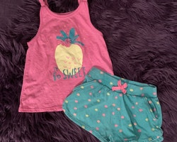 Set med rosa linne dekorerat med bl.a en ananas och ett par gröna shorts med rosa och gula prickar från Primark stl 80