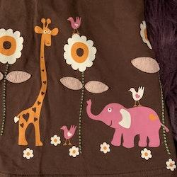 Brun hängselklänning med orange kantband och retrotryck av djur och blommor i vitt, orange och rosa från Lindex stl 74