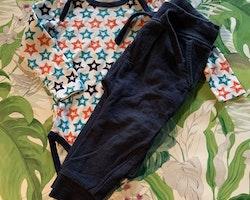 Vit body med stjärnor i mörkblått, turkost och orange samt ett par mörkblå collegebyxor från Name It & NeXT stl 80