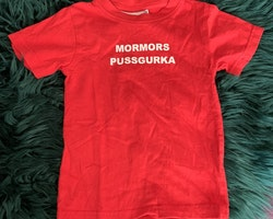 Röd t-shirt med vitt texttryck från Strump snickaren AB stl 86/92