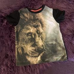 Lejonprydd t-shirt med svart baksida från Adventure stl 98/104