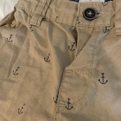 3 delat paket med en mörkblå kortärmad body, en vit linnesbody och ett par beigea shorts, båda med mörkblå ankare stl 74