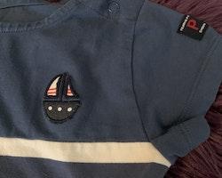 Mörkblå- och vitrandig kortärmad och kortbent jumpsuit med liten båtapplikation från PoP stl 104