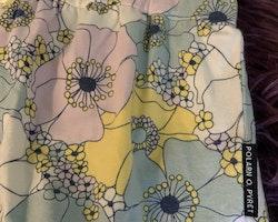 Blommig jumpsuit med volangärmar i ljusrosa, gult, vitt, svart och ljusblått från PoP stl 56
