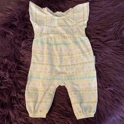 Vit jumpsuit med volangärm och abstrakt mönster i pastelligt grönt, ljusrosa, blått, ljuslila och gult från PoP stl 50