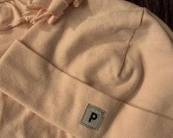 Ljusrosa ärmlös jumpsuit med volanger och matchande tunn mössa med tofsar från PoP stl 62