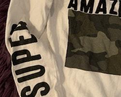 Vit tröja med lite kamouflagemönster i grönt och svart texttryck samt ett par svarta leggings från Primark & Kappahl stl 98 + 104