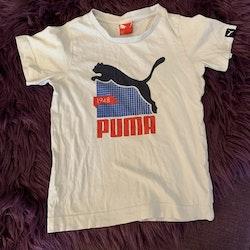 Vit t-shirt med tryck i svart, blått och rött från Puma stl 104
