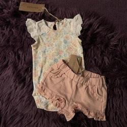 Vit body med hålbroderad volangärm och ett par shorts i vitt med blommönster i senapsgult, ljusblått och rosa från Newbie stl 62