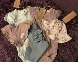 5 delat paket i lila och petrol med två bodies, ett par leggings, en solhatt och en haklapp från Newbie stl 68 + 44/46