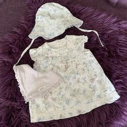 3 delat paket med en vit, blå- och lilablommig volangprydd klänning med matchande solhatt och en haklapp från Newbie stl 62 + 44/46