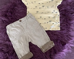 Set med en sköldpadd- och palmprydd ljusgul t-shirt och ett par shorts/byxor i linnelook från Newbie stl 74