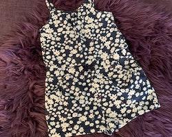 Mörkblå jumpsuit med spagettiband, korta ben och vitt blommömnster från HM stl 98/104