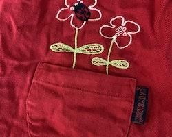 Röd ärmlös klänning med fickor och broderier med blommor och nyckelpiga från Lindex stl 98