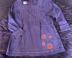 Lila tunika/klänning med blomtryck och broderier i lila och orange från Name it stl 104