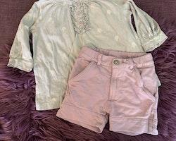 Blågrå topp med vita luftballonger, volanger och lila knappar samt ett par lila shorts från Blingo stl 98/104
