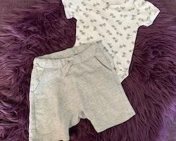 Vit kortärmad body med grå cyklar och ett par gråmelerade shorts från ? & Lindex stl 74