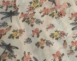 Vit kortärmad och kortbent romper med pastelligt mönster av blommor och trollsländor från Lindex stl 62