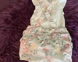 Mintgrön body med volangärm och spets samt ett par mintgröna hängselshorts med volanger och blommönster i rosa, gult och vitt från Newbie stl 74