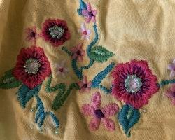 Gul ärmlös sommarklänning med detaljer i rosa och broderade, pärlprydda blommor från Kappahl stl 110/116