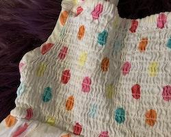 Vit klänning med smocköverdel och prickar i rosa, gult, orange och turkost från HM stl 116