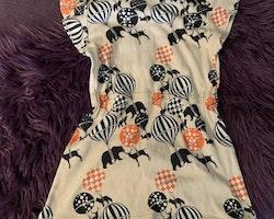 Ljustaprikosfärgad klänning med volangärm och ett svart, vitt och persikofärgat mönster med djur och luftballonger från Filemon Kid stl 116/122