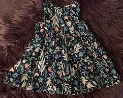 Mörkblå ärmlös klänning med flerfärgat mönster av blommor, jordgubbar och fjärilar från HM stl 74
