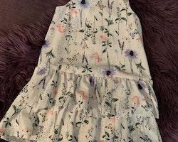 Vit ärmlös klänning med volanger och somrigt mönster med blommor och fjärilar från HM stl 116