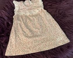 Vit ärmlös klänning med vita hålbroderade volanger och gammelrosa och grönt blommönster från Newbie stl 74