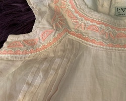 Ljusrosa asymmetrisk klänning med volangärm och broderier i vitt och neonrosa från NeXT stl 6-9 mån