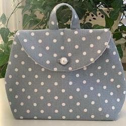 Lyseblå pung med hvite prikker