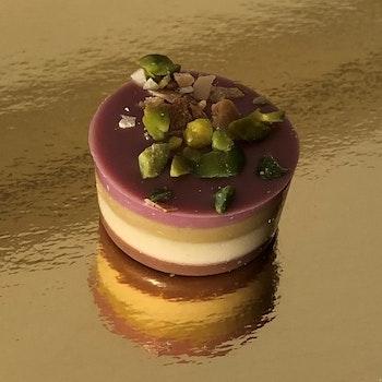 Mandel nougat tårta med pistagemassa, gräddnougat & Ruby choklad. (INNEHÅLLER NÖTTER)