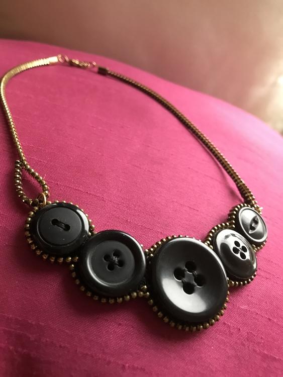Halsband av återbrukade knappar och dragkedjor.