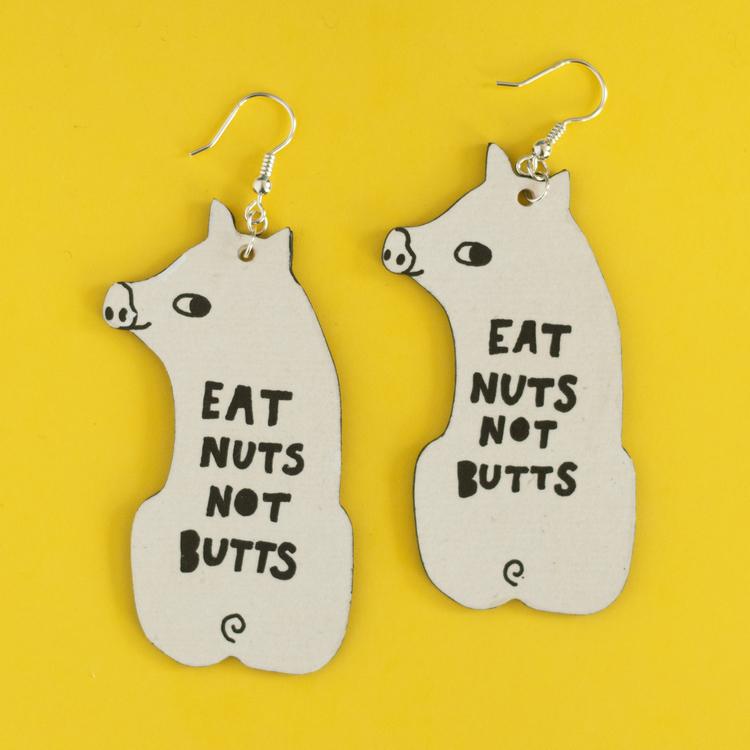 """Örhängen av reklamskylt  """"Eat nuts not butts"""""""
