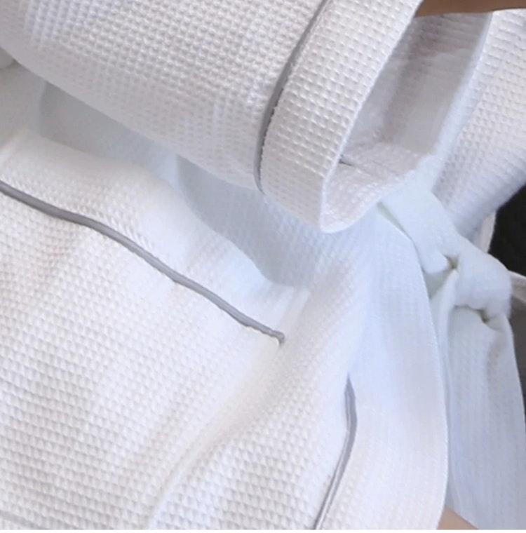 Vit exklusiv badrock i 100 % bomull, våfflat mönster med en stilren grå dekorrand.