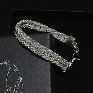 Nålbundet armband, silverfärgat, genombrutet mönster