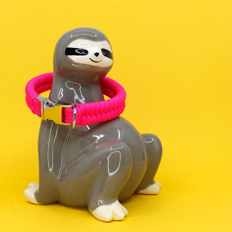 Neonrosa hundhalsband knutet för hand i paracord – en väldigt slitstark nylonlina. Modell: sengångare.