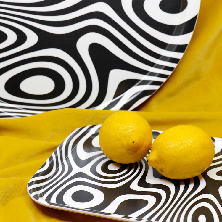 Detaljbild på två brickor och två citroner. Brickorna är svartvita och har ett abstrakt, snurrigt och hypnotiskt mönster.