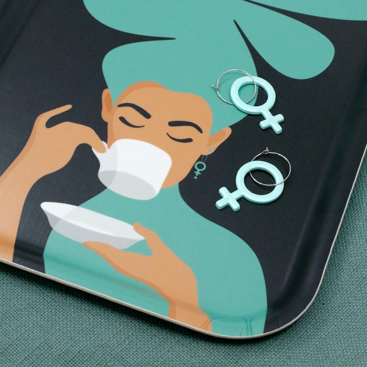 Detaljbild på en turkos bricka med motivet Kaffekvinna. Kaffekvinnan har stort böljande hår, bär ett feministörhänge och njuter av en kopp kaffe. På brickan ligger två mintfärgade feministörhängen.