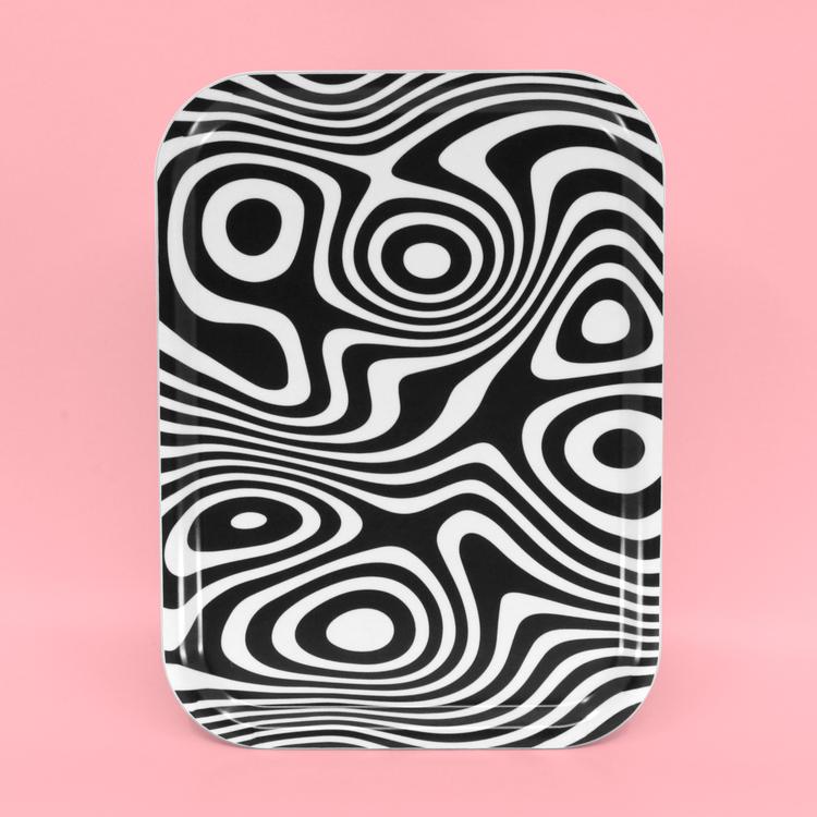 Liten rektangulär svartvit bricka med ett abstrakt, snurrigt och hypnotiskt mönster.