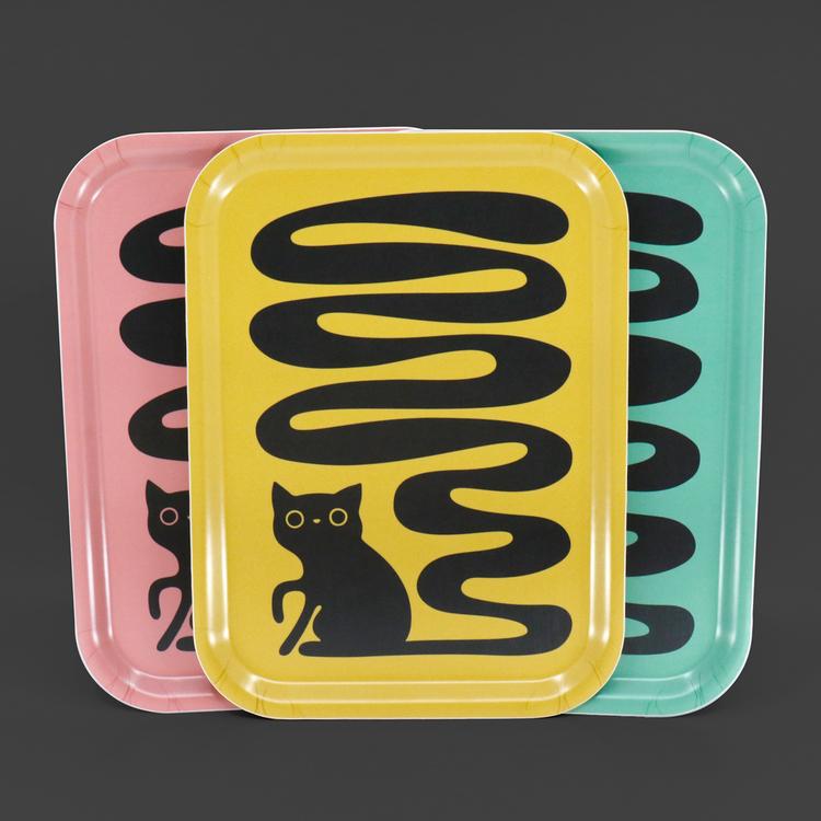 Tre rektangulära brickor i färgerna gul, rosa och turkos med motiv av en svart katt med en väldigt lång och svängig svans. En svanskatt.