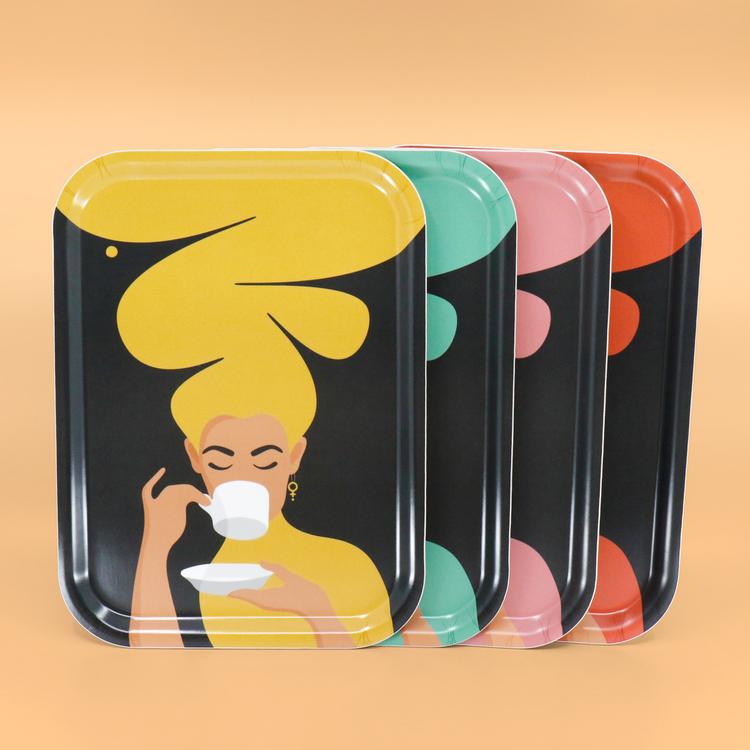 Fyra rektangulära brickor med fyra olika färger (gul, turkos, rosa och röd) av motivet Kaffekvinna. Kaffekvinnan har stort böljande hår, bär ett feministörhänge och njuter av en kopp kaffe.