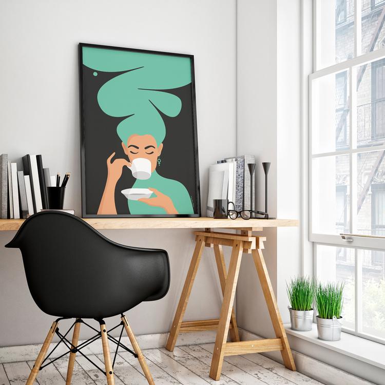 Poster med den turkosa Kaffekvinnan inramad på ett skrivbord. Format 50x70 cm.
