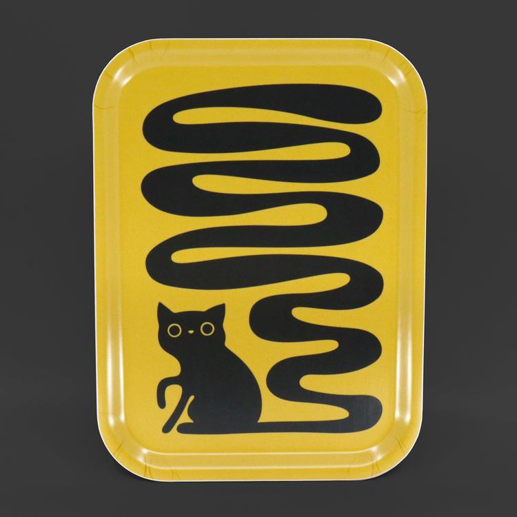 Rektangulär gul bricka med en svart katt som har en väldigt lång svängig svans. En svanskatt.