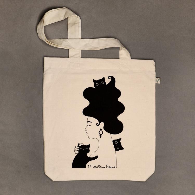 Ekologisk tygpåse / tygkasse med långa handtag och ett svart screentryck med motivet Kattkvinnan – en kvinna med stort böljande hår, örhänge i form av en venussymbol / kvinnosymbol i örat och tre busi