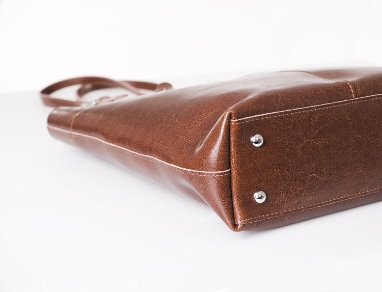 Kasse i brunt skinn med långa handtag