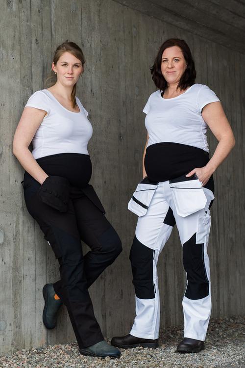 Två gravida kvinnor lutar sig mot en betongvägg och bär arbetskläder för gravida.