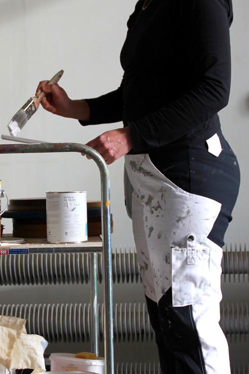Kvinna i målarbyxor som håller i en pensel.