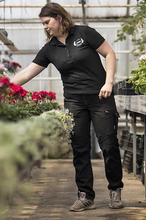 En kvinna i svarta arbetskläder som rensar blommor i ett växthus